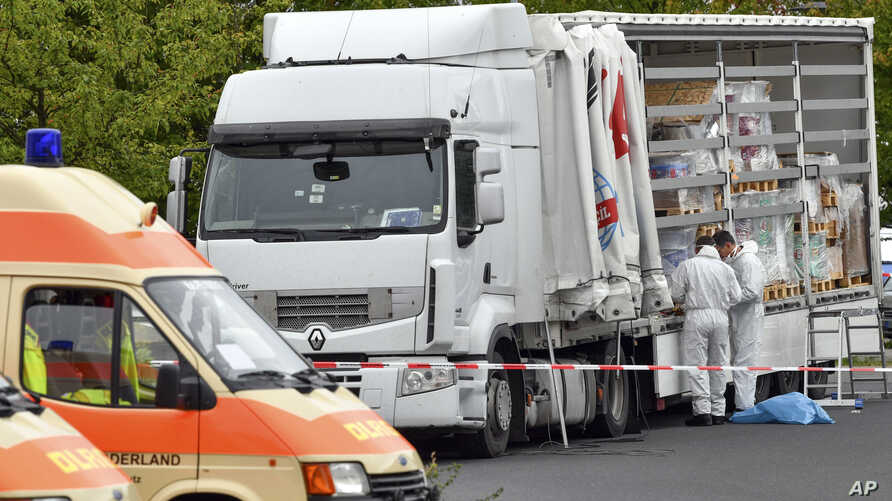 Policemen investigate a truck near a police station in Frankfurt, Germany, Sept. 16, 2017. Germany's federal police say they stopped the truck near the German-Polish border with 51 people inside, among them 17 children.