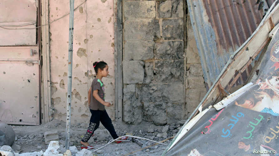 A girl walks on debris in a rebel-held part of the southern city of Deraa, Syria, July 9, 2017.