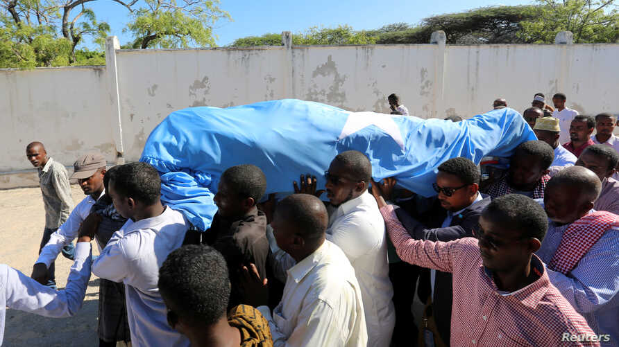 FILE -  Relatives carry the dead body of Somalia's public works minister Abbas Abdullahi Sheikh Siraji who was shot and killed in Somalia's capital Mogadishu, May 4, 2017.