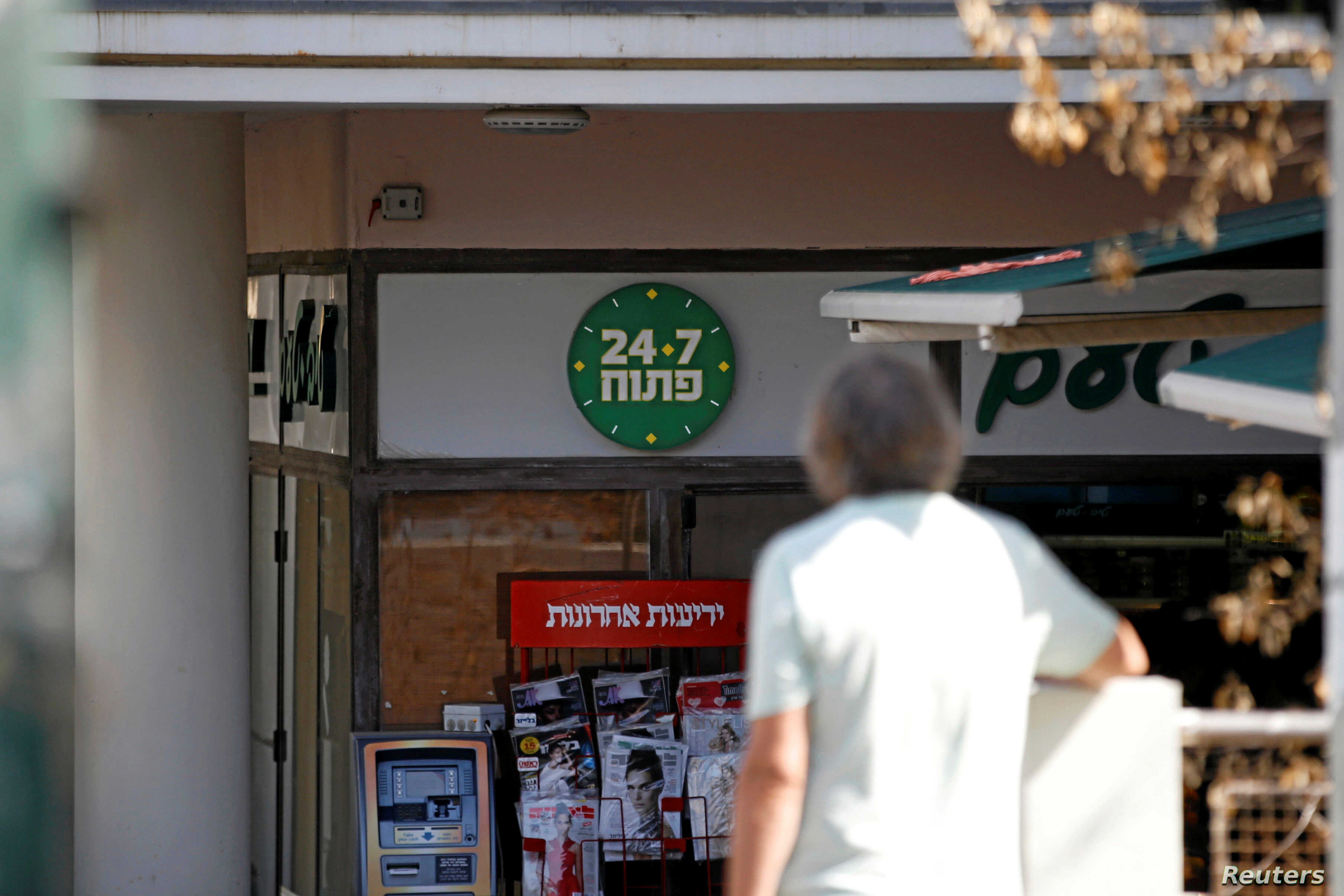 "A man stands nearby as a ""24/7"" open sign is seen at the entrance of a food store in Tel Aviv, Israel, September 20, 2016."