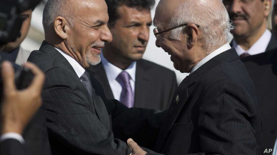 Pakistan's adviser on National Security and  Foreign Affairs Sartaj Aziz, right, greets Afghan President Ashraf Ghani at Chaklala airbase in Rawalpindi, Pakistan, Friday, Nov. 14, 2014.