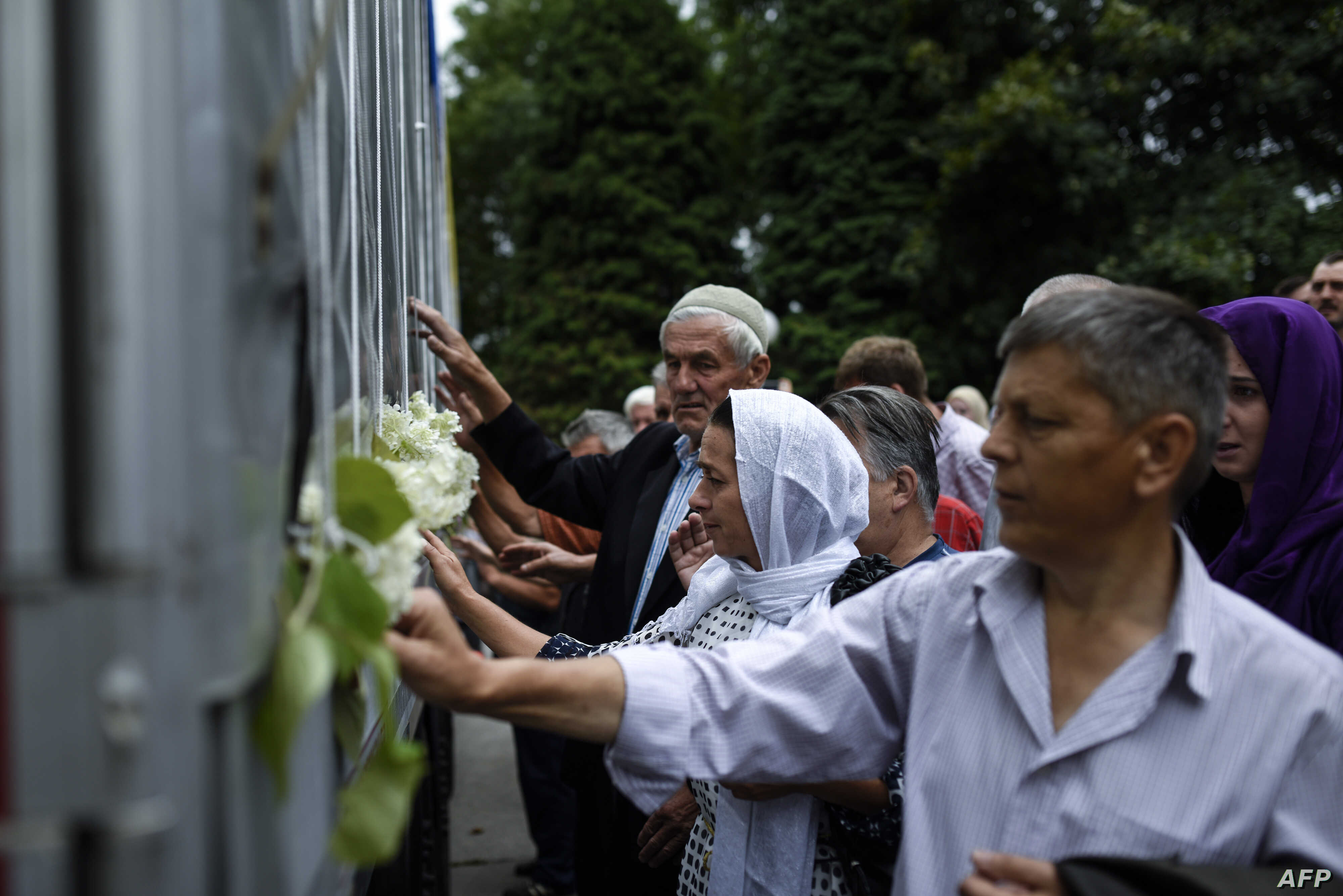 Bosnian muslims reacts as they touch a truck carrying 136 coffins of newly identified victims of the 1995 Srebrenica massacre in the town of Visoko, near Sarajevo, July 9, 2015.