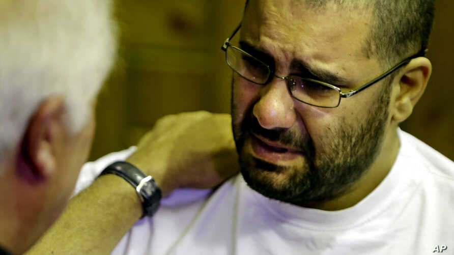 FILE - Prominent Egyptian blogger Alaa Abdel-Fattah, grieves as he receives condolences for his father, Ahmed Seif, at Omar Makram Mosque in Cairo, Egypt, Aug. 30, 2014.