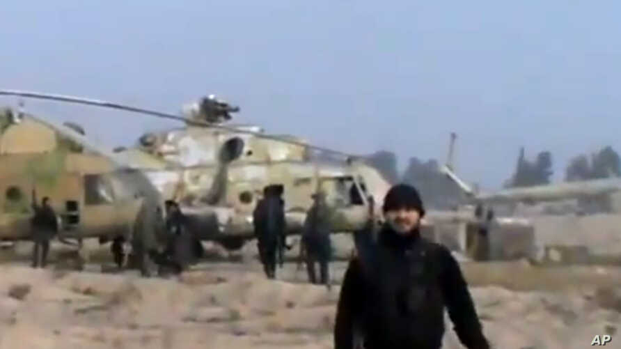 In this image taken from video obtained from the Ugarit News, which has been authenticated based on its contents and other AP reporting, Syrian rebels capture a helicopter air base near the capital Damascus after fierce fighting in Syria, on Sunday, ...