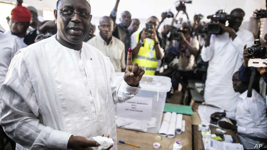 Senegal's incumbent President Macky Sall casts his vote during the presidential election at a polling station in Fatick, Senegal, Feb. 24, 2019.