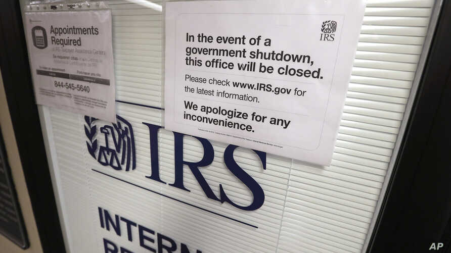 FILE- Doors at the Internal Revenue Service (IRS) in the Henry M. Jackson Federal Building are locked and covered with blinds as a sign posted advises that the office will be closed during the partial government shutdown in Seattle,  Jan. 16, 2019.