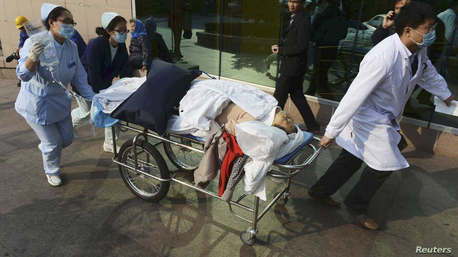 FILE - An injured woman is transferred to a hospital after an explosion at a Sinopec Corp oil pipeline in Huangdao, Qingdao, Shandong Province.