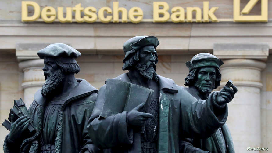 A statue stands next to the logo of Germany's Deutsche Bank in Frankfurt, Germany, Sept. 30, 2016.