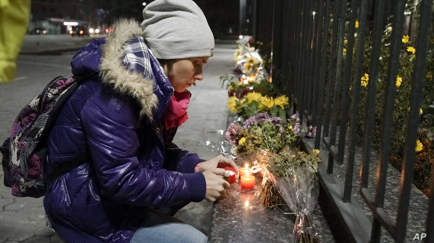 A Ukrainian woman lights a candle in front of the Russian Embassy in Kyiv to pay tribute to victims of a Russian plane crash in the Sinai Peninsula, Oct. 31, 2015.