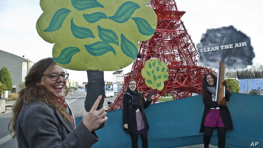 """NGO representatives shout """"clean the air, plant a tree,"""" near a reproduction of the Eiffel Tower at the U.N. Climate Change Conference in Le Bourget, north of Paris, Dec. 5, 2015."""