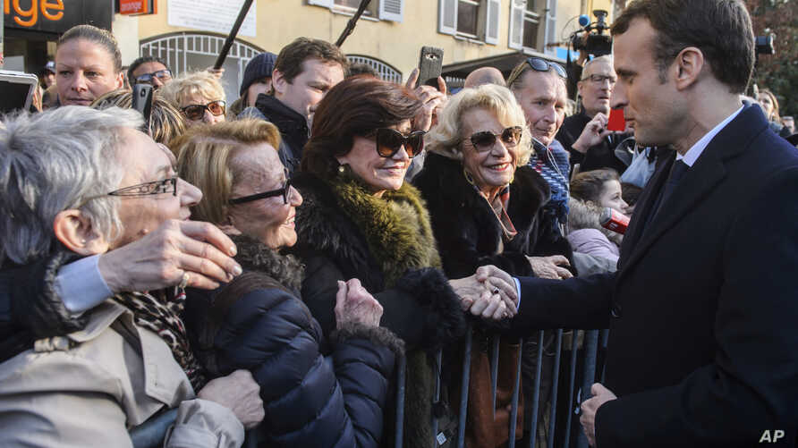 French president Emmanuel Macron meets residents as he walks to the city hall of Ajaccio, Feb. 6, 2018 in Ajaccio, Corsica island. Macron made a vibrant plea for the unity of the French Republic as he arrived Tuesday in Corsica for a two-day visit.