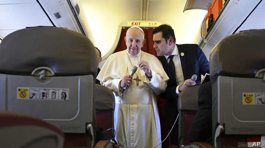 Pope Francis, flanked by interim director of Holy See Press Office, Alessandro Gisotti, speaks to reporters on board the flight back to Rome from a two-day trip to Morocco, Sunday, March 31, 2019.