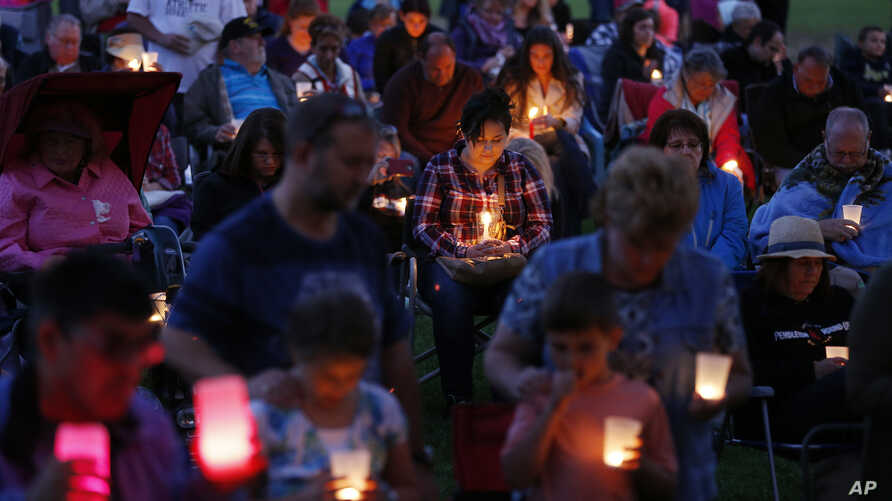 People bow their heads in prayer during a vigil Saturday, Oct. 3, 2015, in Winston, Oregon.