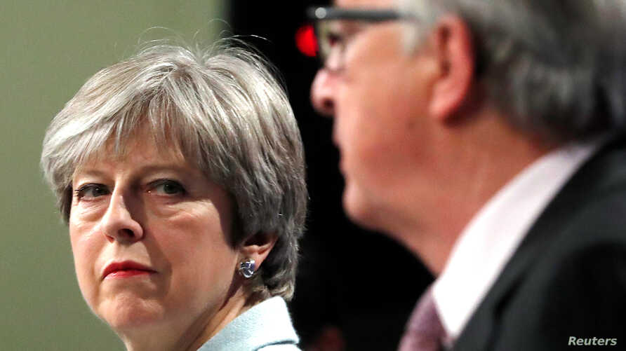 Britain's Prime Minister Theresa May and European Commission President Jean-Claude Juncker hold a news conference at the EC headquarters in Brussels, Dec. 8, 2017.
