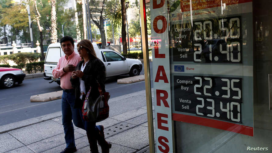 People walk pass a board displaying the exchange rate of Mexican peso against the U.S. dollar in Mexico City, Jan. 11, 2017.