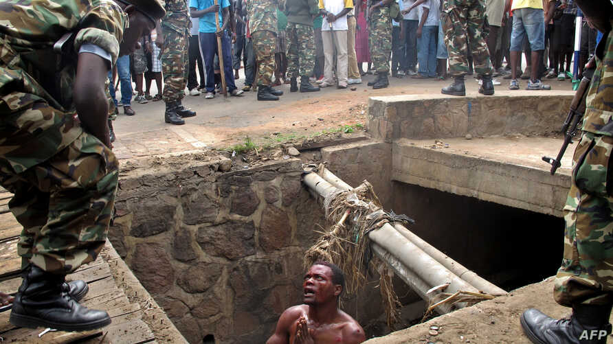FILE - A man begs for help from the military as he stands in a drain where he had hidden to escape a lynch mob at the Cibitoke district of Burundi's capital, Bujumbura. International judges have approved the opening of a full investigation into alleg...