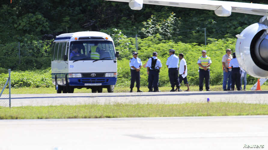 Asylum seekers are pictured being transported from an aircraft to a bus upon their arrival on the island of Nauru, September 14, 2012. Australia has flooded Nauru with money since 2012, when the island became a key plank in its controversial policy o