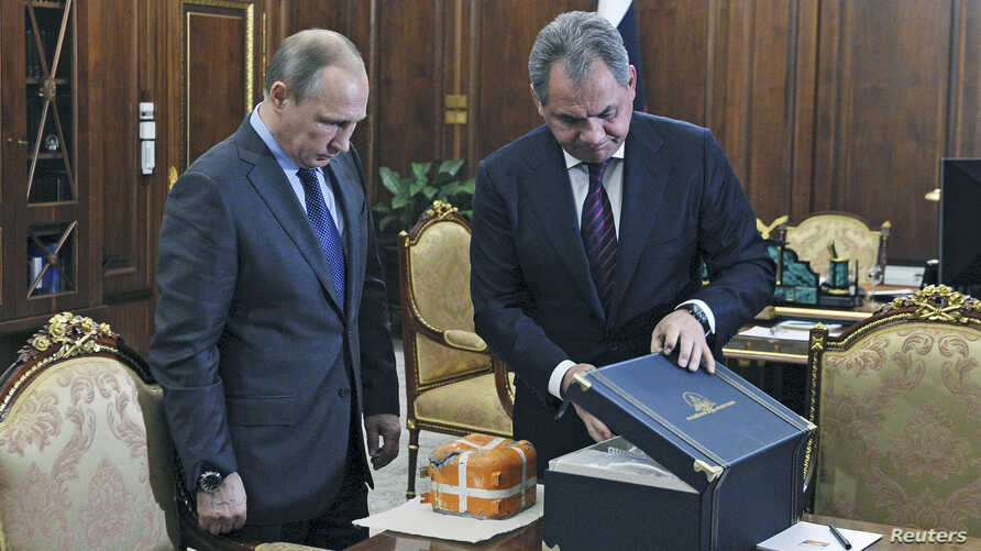 Russian Defense Minister Sergei Shoigu (R) presents to Russian President Vladimir Putin the parametric flight recorder of the downed SU-24 jet at the Novo-Ogaryovo state residence outside Moscow, Russia, Dec. 8, 2015.