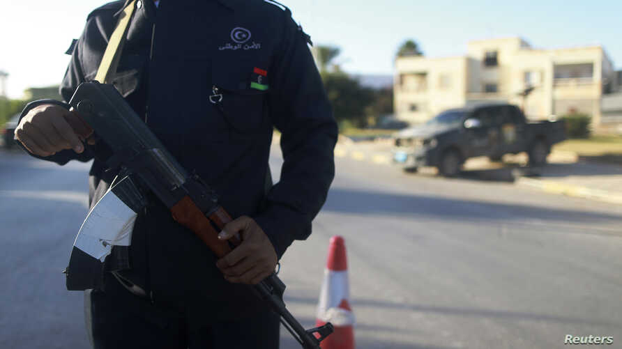 A security officer stands with his weapon on a road leading to a police station in Benghazi, Dec. 4, 2014.