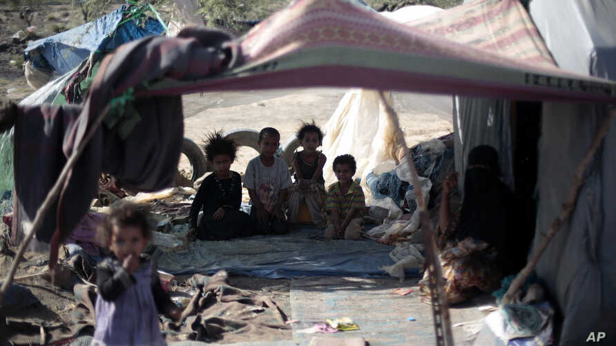 FILE - Displaced children pose for a photo as they sit in their family's tent at a camp for internally displaced people in the outskirts of Sana'a, Yemen, June 8, 2016.