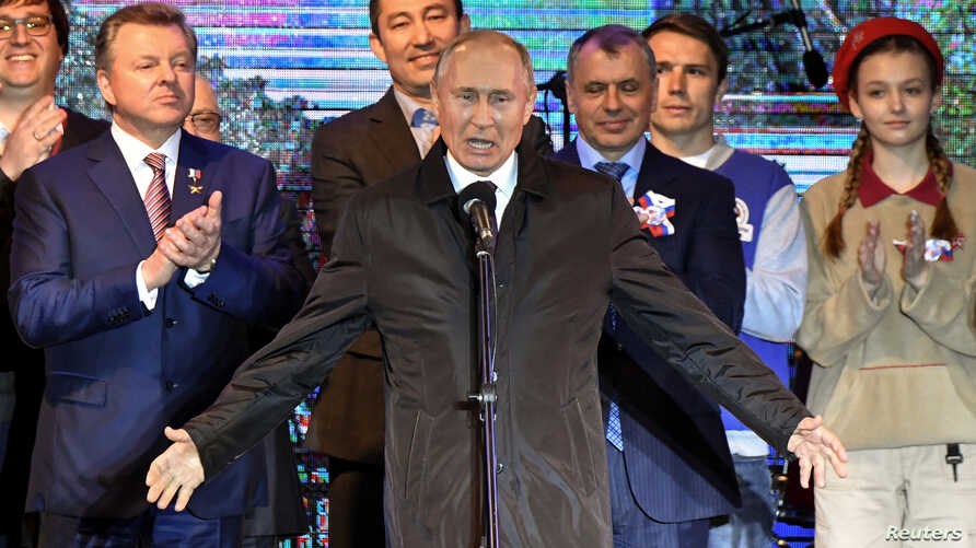 Russian President Vladimir Putin addresses the crowd during a concert marking the fifth anniversary of Russia's annexation of Crimea, in Simferopol, March 18, 2019.
