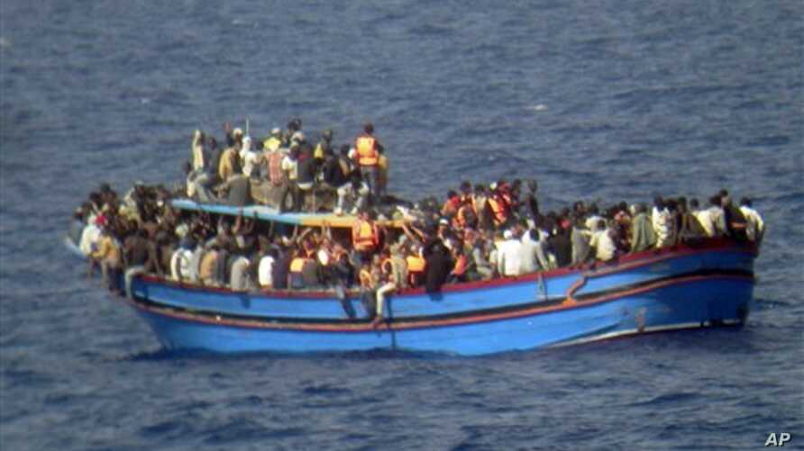 In this photo released by the Italian Navy on Monday and taken on Sunday, June 29, 2014, a boat overcrowded with migrants is pictured in the Mediterranean Sea. The bodies of some 30 would-be migrants were found in in the hold of a packed smugglers' b