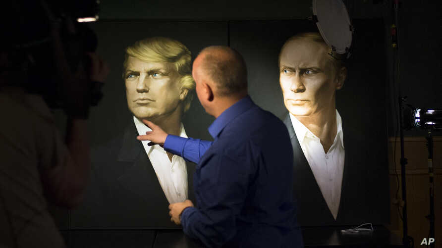 A journalist points at a portrait of U.S. President-elect Donald Trump, with a portrait of Russian President Vladimir Putin at right, during a live telecast of the U.S. presidential election in the Union Jack pub in Moscow, Russia, Nov. 9, 2016.
