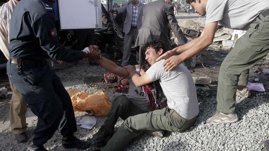 Brothers of an Afghan mini-bus driver who was killed in a suicide bombing cry at the scene, Sept. 18, 2012 in Kabul, Afghanistan.
