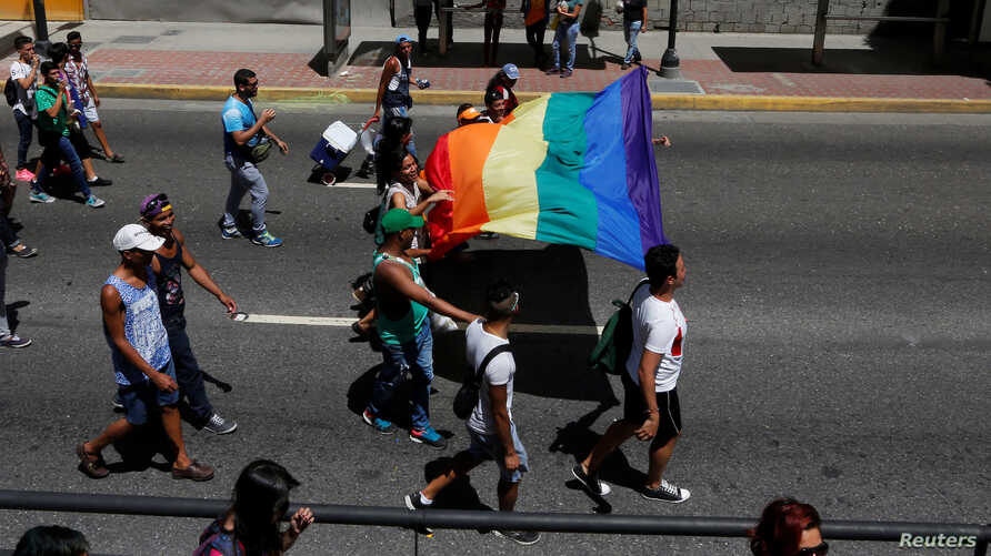 Revellers hold a rainbow flag as they take part in the gay pride parade in Caracas, Venezuela, July 3, 2016.