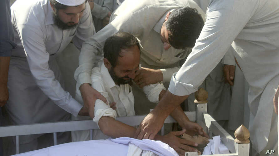 Villagers comfort a family member of Haroon Khan, a journalist killed the previous day in Swabi, Pakistan, Oct. 13, 2017.