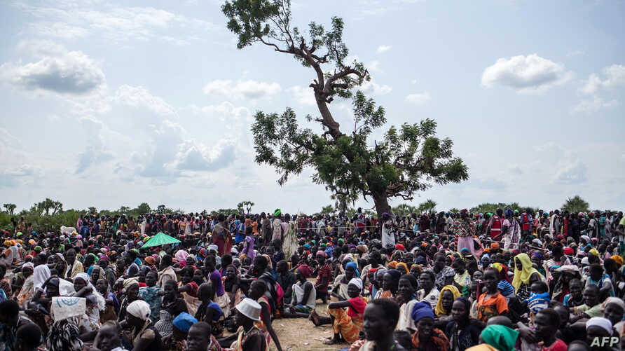 Thousands of people wait in the hot sun near the air drop zone in Leer, South Sudan, July 5, 2014.