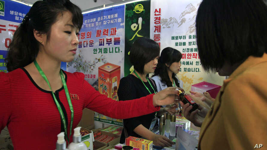 FILE - North Koreans look at products at an international trade fair held Sept. 25, 2017, in Pyongyang.