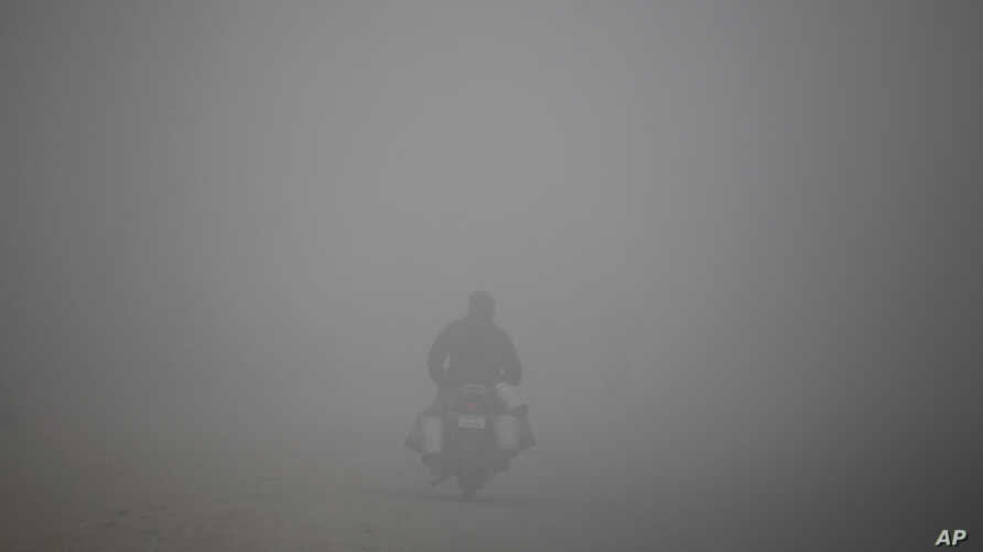 """A man rides a motorcycle on a morning thick with smog on the outskirts of New Delhi, India, Jan. 5, 2019. A Sunday morning rain improved the air quality to """"very poor."""""""