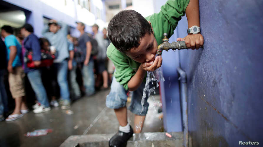 FILE - A migrant child drinks water from tap in Tecun Uman, Guatemala,  October 19, 2018.