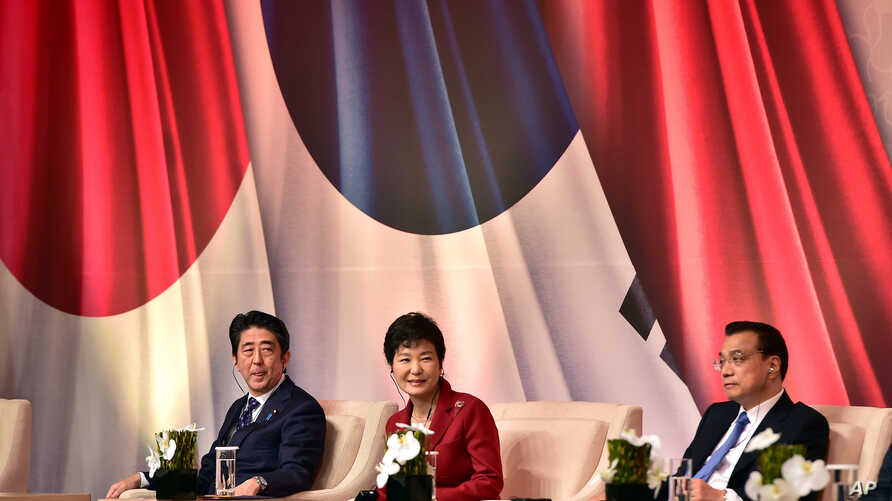 South Korean President Park Geun-hye, center, Japanese Prime Minister Shinzo Abe, left, and Chinese Premier Li Keqiang attend at a business summit in Seoul, Nov. 1, 2015.