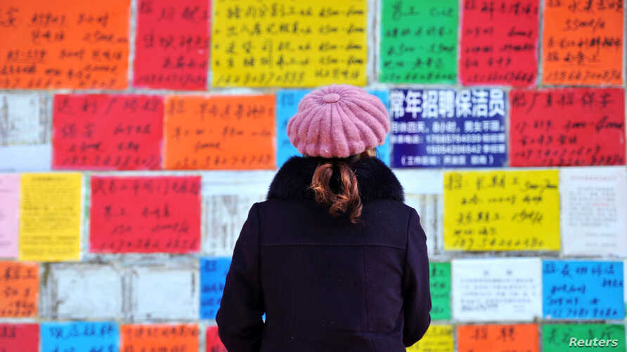 A woman looks at job advertisements on a wall in Qingdao West Coast New Zone in Shandong province, China, Jan. 17, 2019.