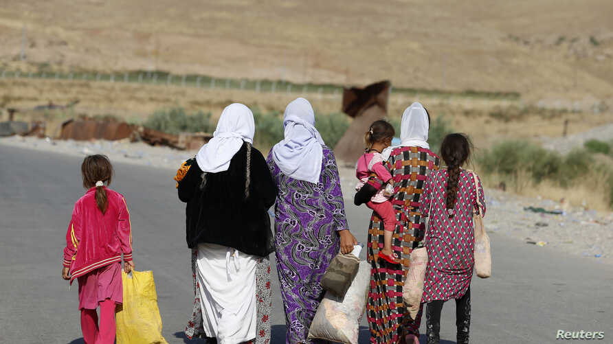 Women and children from the minority Yazidi sect, fleeing the violence in the Iraqi town of Sinjar, walk to a refugee camp after they re-entered Iraq from Syria at the Iraqi-Syrian border crossing in Fishkhabour, Dohuk province, August 14, 2014.