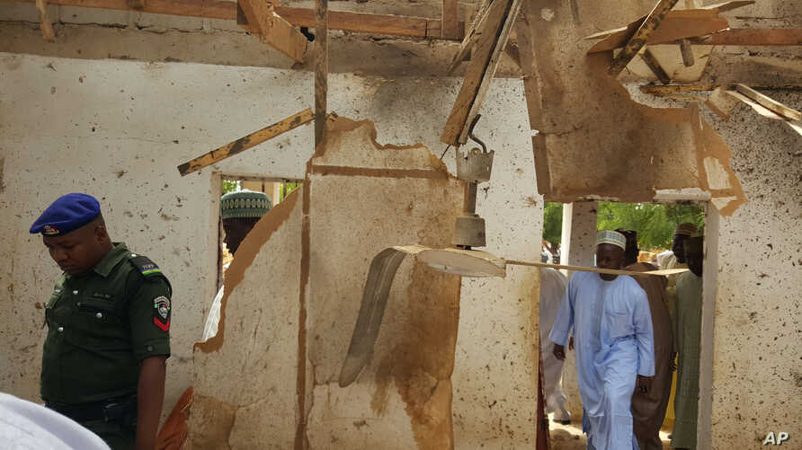 People inspect a damaged mosque following a suicide bomb explosion in Maiduguri, Nigeria on March 16, 2016. Two female suicide bombers killed at least 24 worshippers and wounded 18 in an attack during dawn prayers Wednesday on a mosque on the outskir