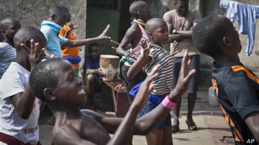 In this photo taken Sunday, Nov. 9, 2014, a dozen children perform a traditional courtship dance from eastern Uganda as part of a platform for changing attitudes among youth using dance, drama and popular hip hop music, at the Treasure Life Center in