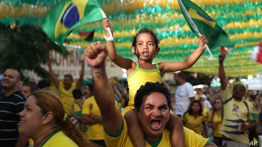 Soccer fans celebrate as they watch on a big screen television, the second goal scored by Brazil's Neymar in the World Cup match against Cameroon, in Manaus, Brazil, June 23, 2014.