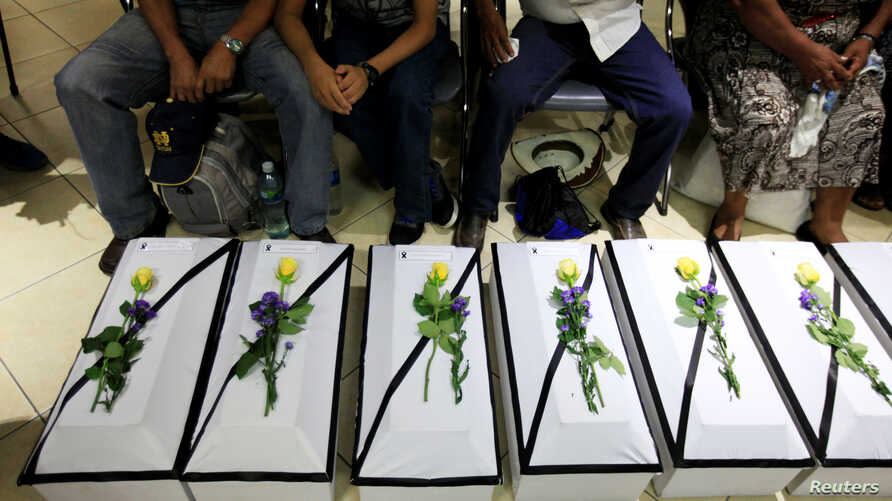 Relatives sit next to the remains of 11 victims of the El Mozote massacre during a ceremony at the Supreme Court of Justice in San Salvador, El Salvador May 20, 2016.