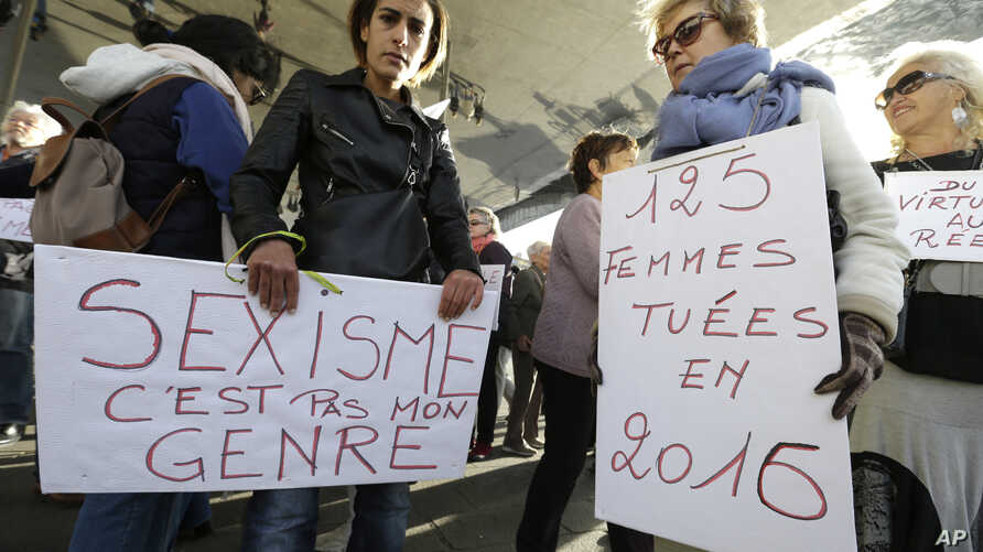 """Women hold placards reading """"Sexism is not my gender,"""" left, and """"125 women killed in 2016"""" during a rally protesting sexual abuse and harassment, in Marseille, southern France, Oct. 29, 2017."""