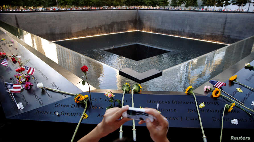A visitor photographs the National September 11 Memorial and Museum on the 15th anniversary of the 9/11 attacks in New York, Sept. 11, 2016.