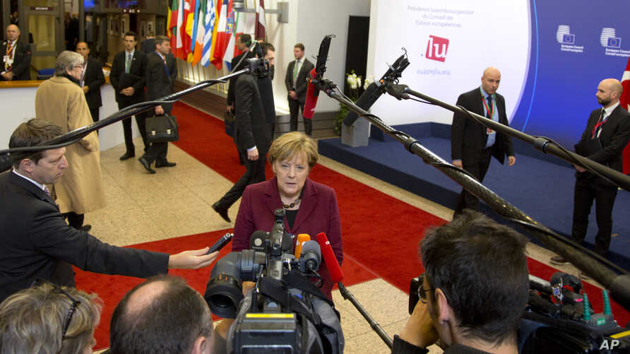 German Chancellor Angela Merkel speaks with the media as she arrives for an EU-Turkey summit at the EU Council building in Brussels, Nov. 29, 2015.