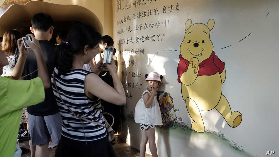 A child poses for photos near a mural depicting Winnie the Pooh in Shanghai, China, Aug. 8, 2018.