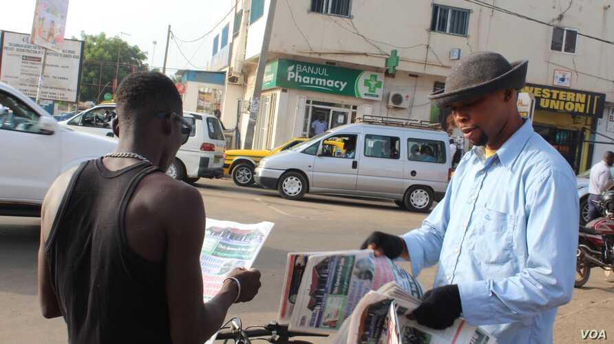 A young man buys a newspaper from a street vendor in Westfield, Banjul, Gambia, June 7, 2017. (S.Christensen/VOA)