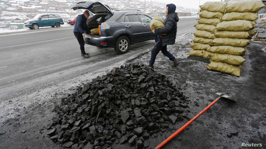 People load coal into a car in Ulaanbaatar, Mongolia as the wave of extreme cold hits the country, Dec. 22, 2016.