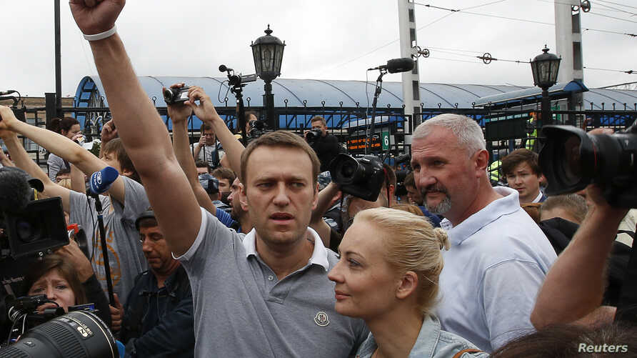 Russian opposition leader Alexei Navalny (L) addresses his supporters after arriving from Kirov, with his wife, Yulia, standing nearby, at a railway station in Moscow, July 20, 2013.