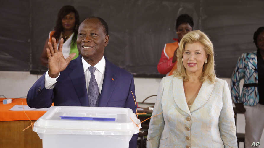 Ivory Coast's president Alassane Ouattara, left, waves after casting his ballot with his wife, Dominique Ouattara, right, at a polling station during elections in Abidjan, Ivory Coast, Sunday Oct. 25, 2015.