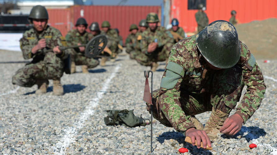FILE - An Afghan soldier digs up a mine during a drill at Camp Shaheen, a training facility for the Afghan National Army, located west of Mazar-i-Sharif, Afghanistan, Dec. 13, 2014.